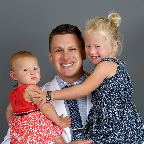 Dr Vetter, a dentist in Fargo, ND holding his young daughters