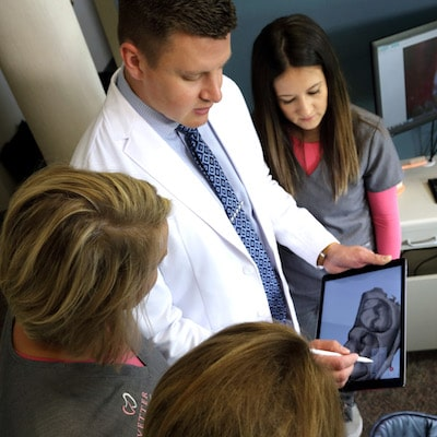 Your family dentist in Fargo, Dr. Vetter, and his team standing and looking at the iPad with images on it.