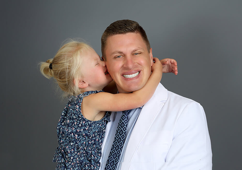 Dr. Vetter, a dentist in Fargo, ND, being hugged by his daughter